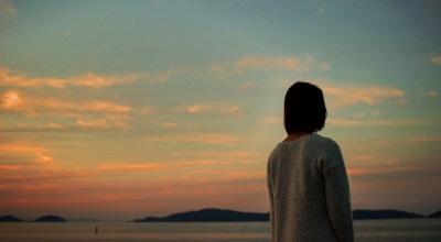 夕暮れの海に立つ女性